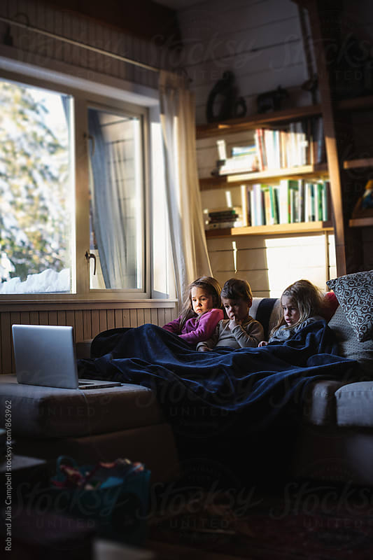 Three kids watching laptop inside during winter day by Rob and Julia Campbell for Stocksy United