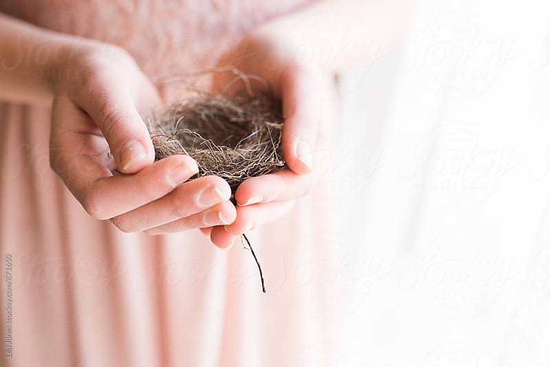 Young woman holding a nest in her hands by Léa Jones for Stocksy United