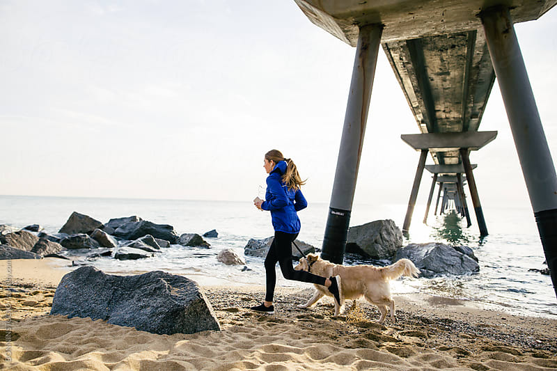 Side view of a woman running with her dog on the beach. by BONNINSTUDIO for Stocksy United