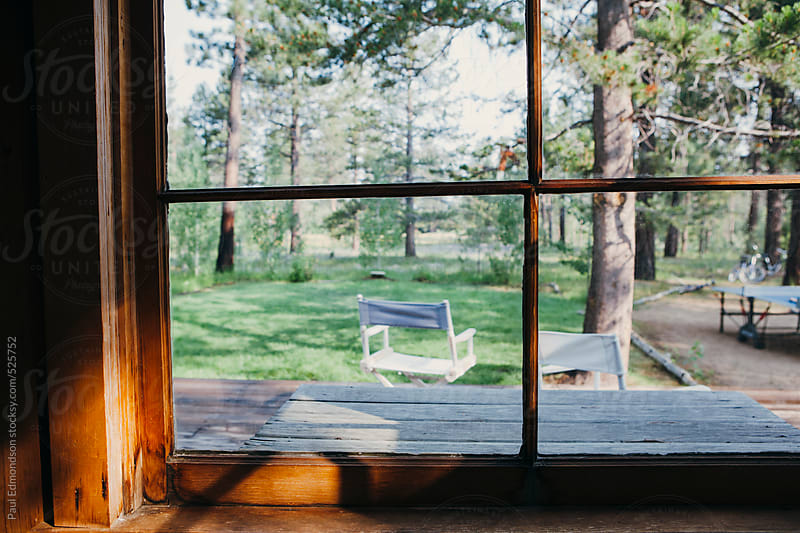 View out window of rustic cabin in the mountains by Paul Edmondson for Stocksy United