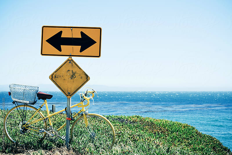 Old yellow bike tied up to an arrow street sign on a coastal highway by Carolyn Lagattuta for Stocksy United