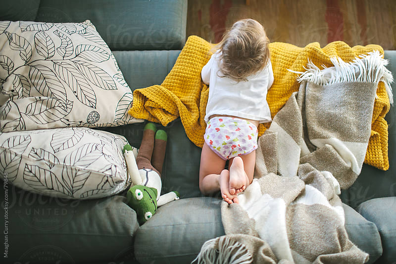 child laying on the couch  by Meaghan Curry for Stocksy United