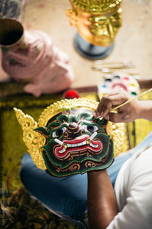 Hands painting 'Hua Khon' traditional mask for Thai performing arts by Nabi Tang for Stocksy United