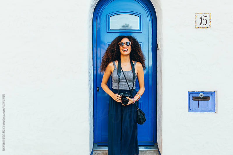 Portrait of a chic tourist smiling in front of a blue door.  by BONNINSTUDIO for Stocksy United