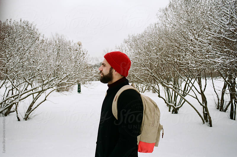 Man among trees covered with snow by Lyuba Burakova for Stocksy United