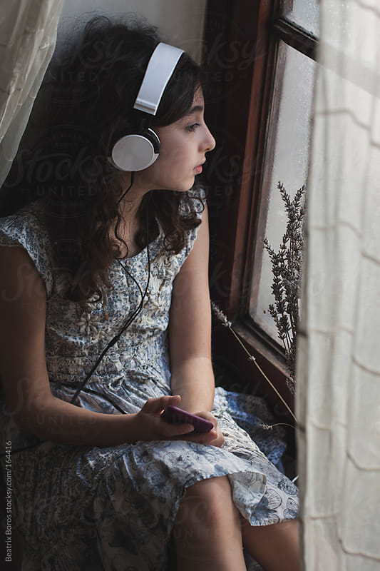 Girl listening to music with headphones at the window by Beatrix Boros for Stocksy United