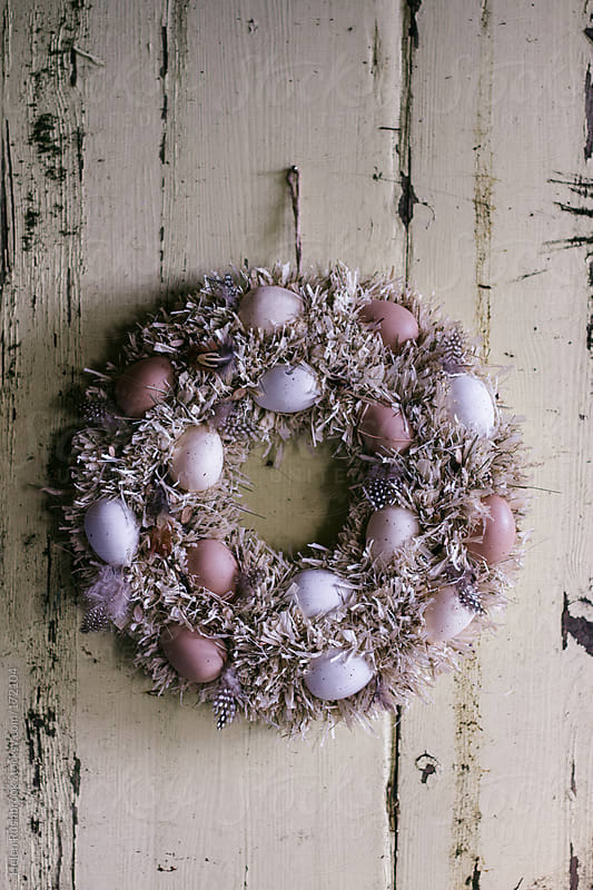 Easter wreath on a dilapidated door by Helen Rushbrook for Stocksy United
