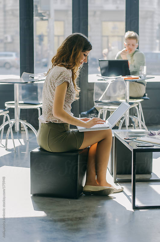 Young businesswoman sitting in a cafe with laptop by Aleksandra Jankovic for Stocksy United