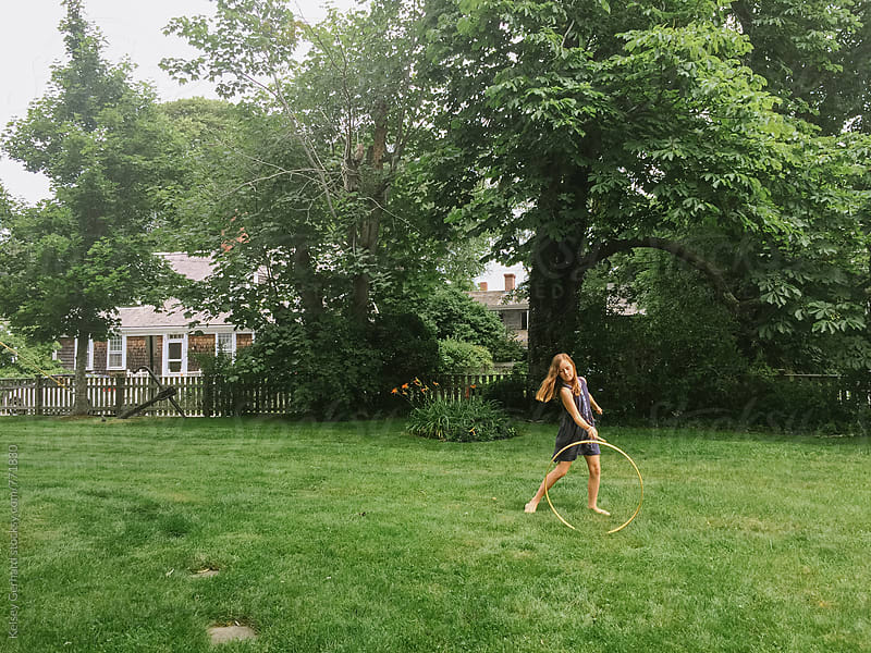 A girl plays with a hoop stick in the yard. by Kelsey Gerhard for Stocksy United