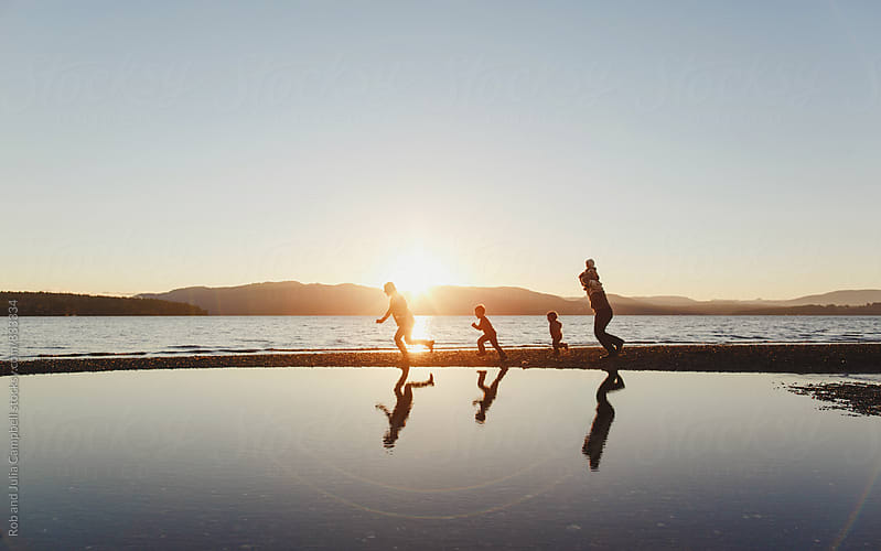 Young family running along the ocean beach at sunset by Rob and Julia Campbell for Stocksy United