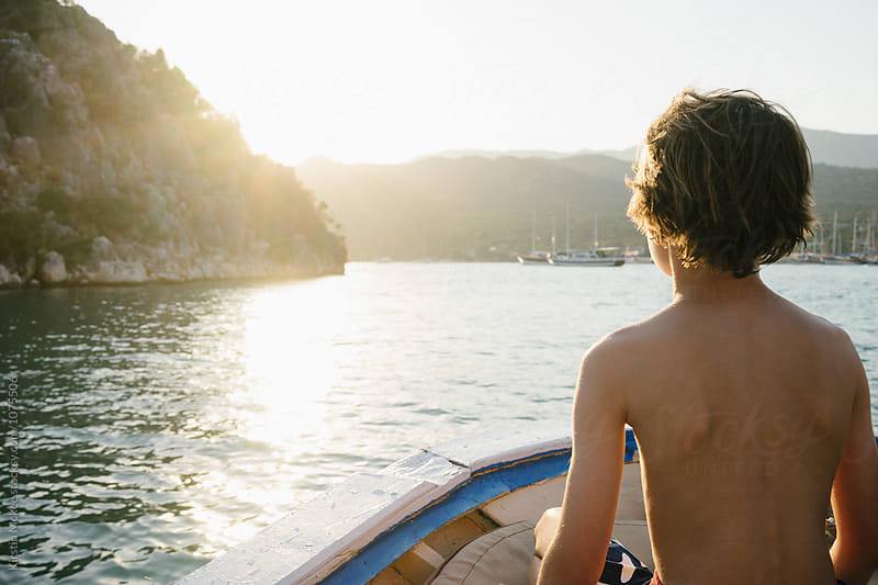 Boy siting on front of moving boat at sunset by Kirstin Mckee for Stocksy United