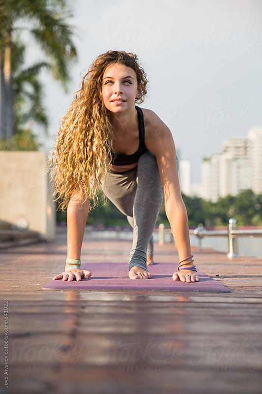 Beautiful young woman in a lunge yoga pose practicing outdoors  by Jovo Jovanovic for Stocksy United