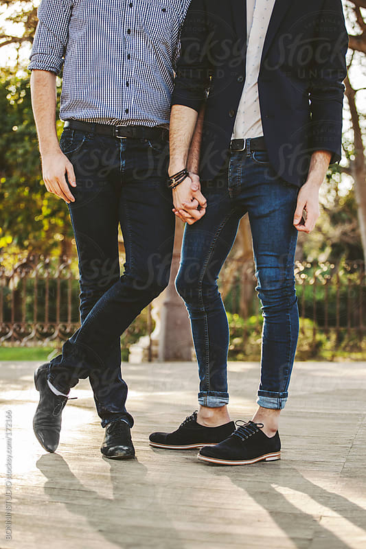 Cropped view of a gay couple holding hands on park. by BONNINSTUDIO for Stocksy United