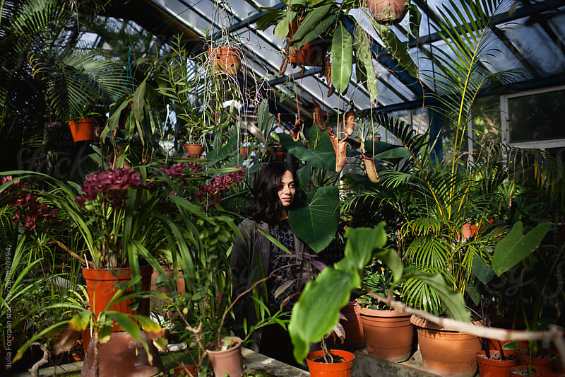 Woman at the centre of plants in a hothouse. by Julia Forsman for Stocksy United