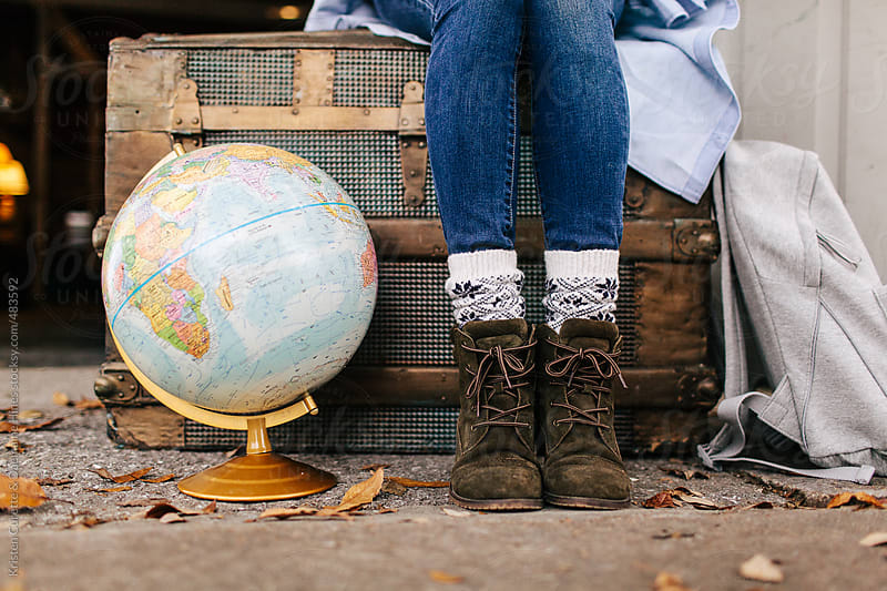 A woman sitting on an antique storage chest with a world globe beside her.  by Kristen Curette Hines for Stocksy United