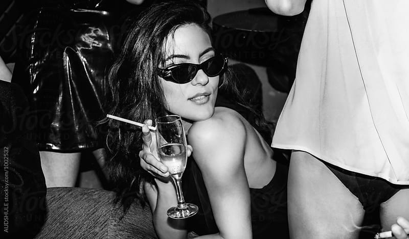 Posh female with glass of champagne and cigarettes on party. by Audrey Shtecinjo for Stocksy United