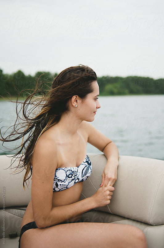 girl on pontoon boat with wind blowing hair by michelle edmonds for Stocksy United