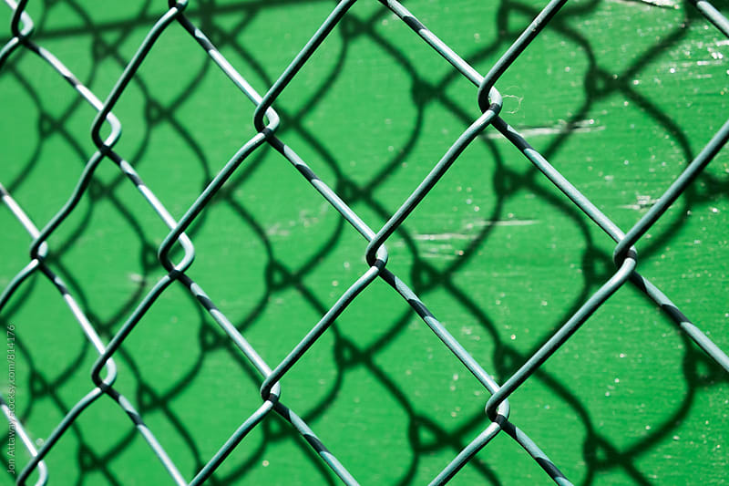 Chain link fence against bright green paint by Jon Attaway for Stocksy United
