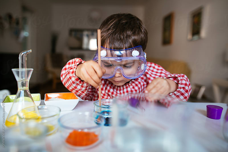 Little boy with glasses making experiments at home. by BONNINSTUDIO for Stocksy United