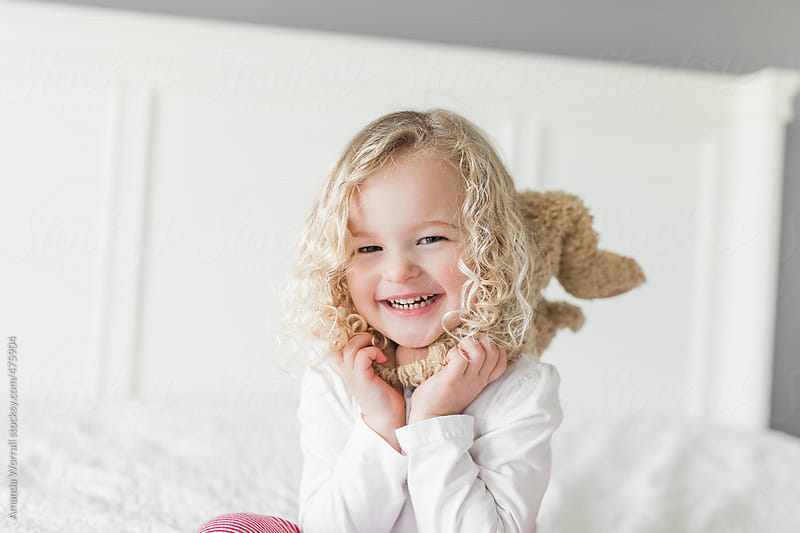 Smiling young girl playing with teddy bear by Amanda Worrall for Stocksy United