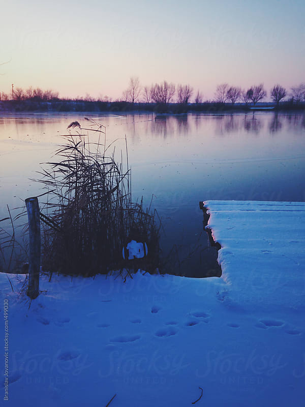 Dock covered with snow on the lake by Brkati Krokodil for Stocksy United
