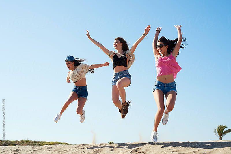 Cheerful girls jumping on beach by Guille Faingold for Stocksy United