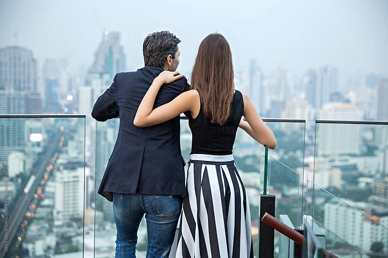Backs of a stylish young couple embracing and enjoying the city view in a modern rooftop bar  by Jovo Jovanovic for Stocksy United