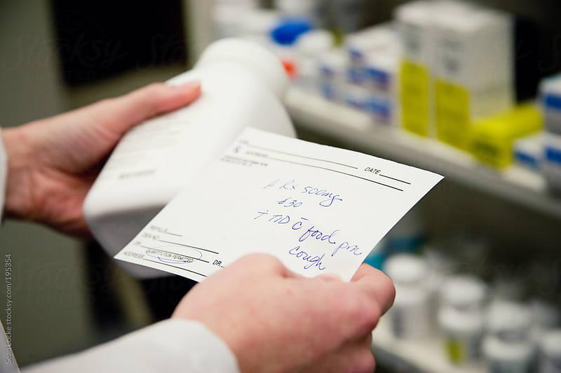 Pharmacy: Pharmacist Reads Doctor Prescription by Sean Locke for Stocksy United