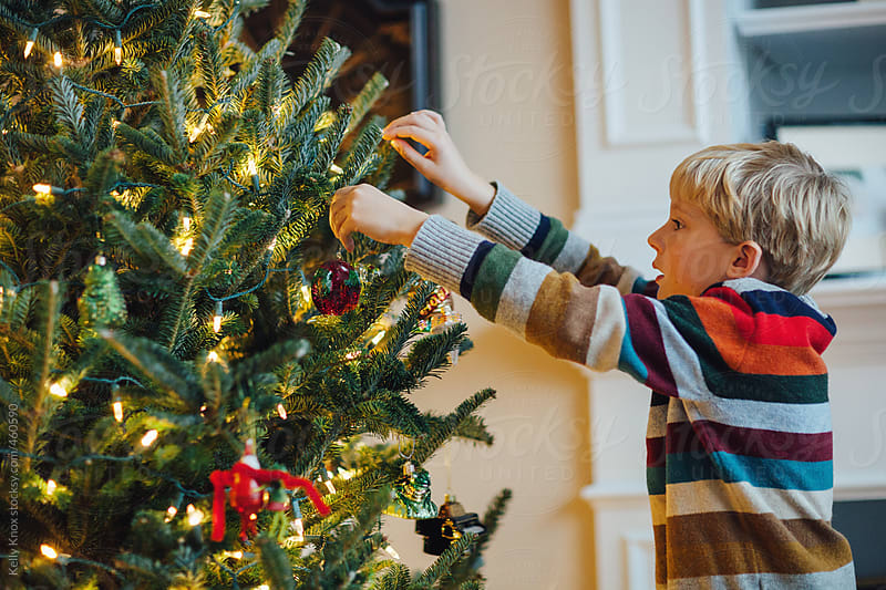child decorating a Christmas tree by Kelly Knox for Stocksy United