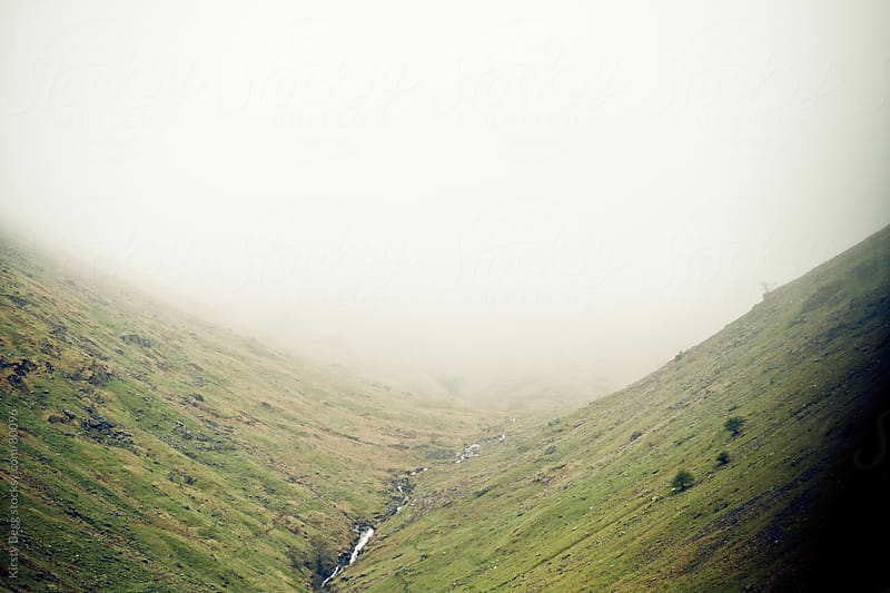 Green valley with fog rolling down by Kirsty Begg for Stocksy United