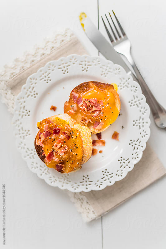Runny Soft-Cured Egg Yolk on Baguet with Bacon  by suzanne clements for Stocksy United