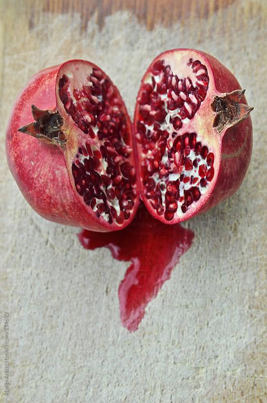 Sliced promegranate on wood plate by Marija Anicic for Stocksy United