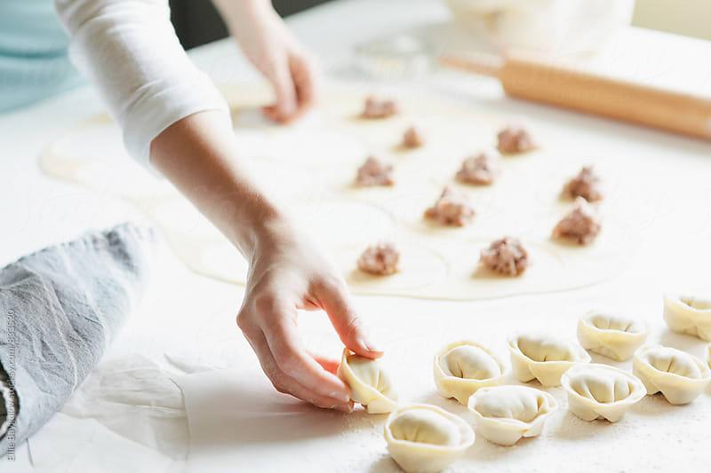 Woman making meat dumplings by Ellie Baygulov for Stocksy United
