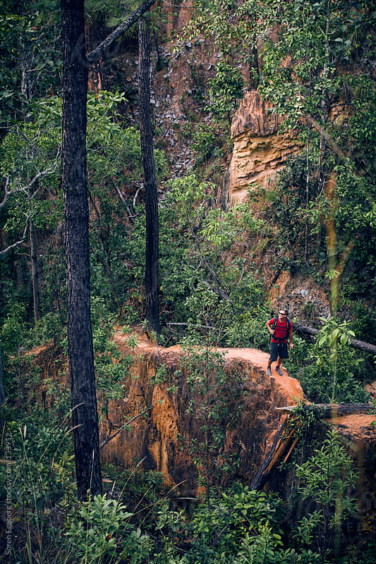 Man in red shirt and backpack hiking on narrow jungle trail. by Soren Egeberg for Stocksy United