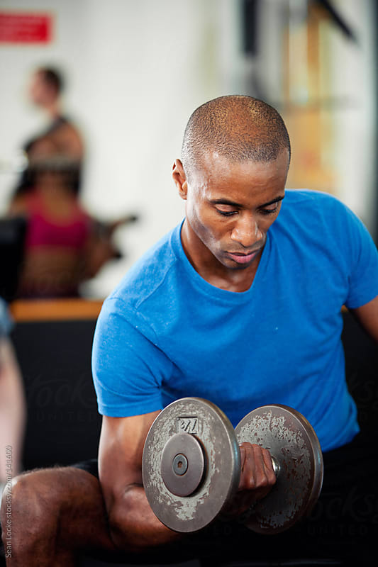 Gym: Man Concentrating on Bicep Curls by Sean Locke for Stocksy United