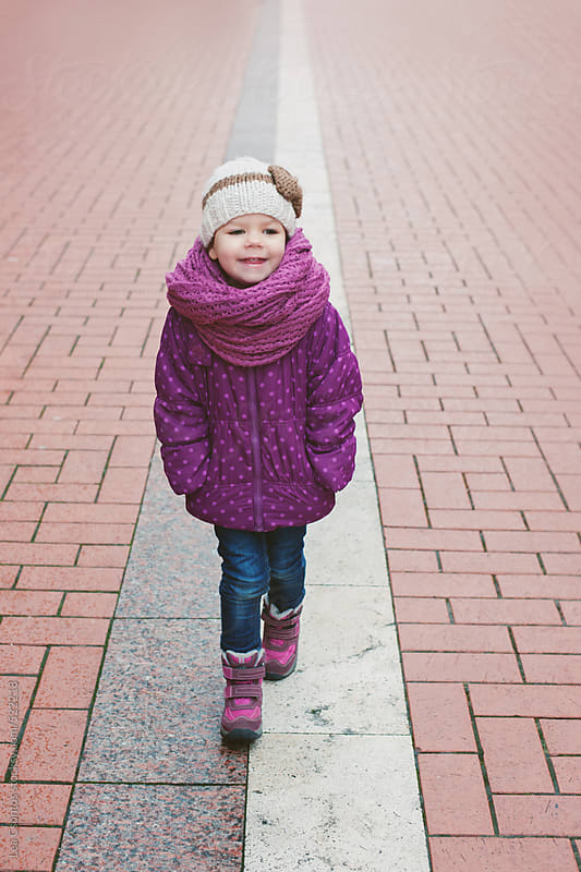 Little girl walking confidently on a street wearing a purple jacket and scarf in cold weather by Lea Csontos for Stocksy United