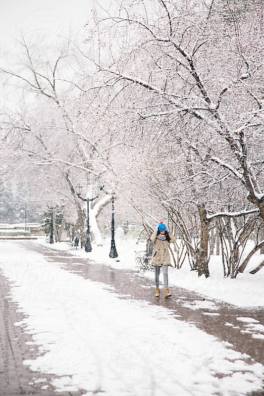 Young woman walking alone in snowy park by Danil Nevsky for Stocksy United