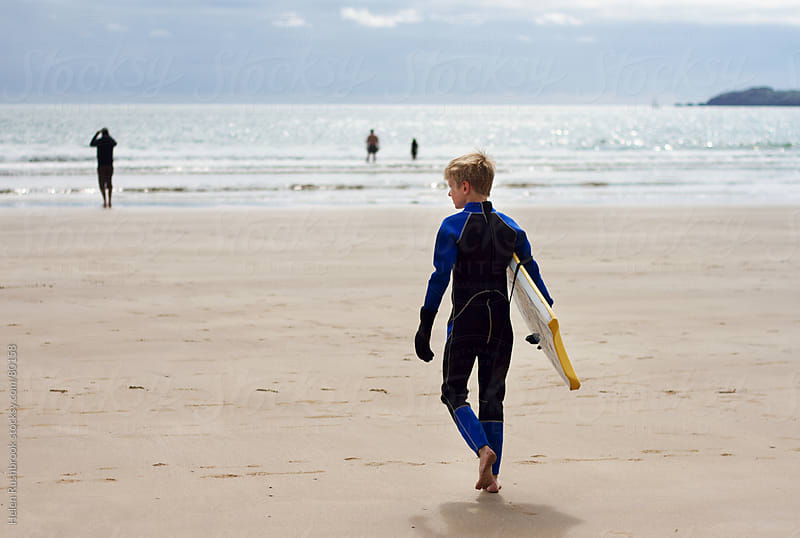 A Pre-teen boy wearing a wetsuit walking to the sea with his body board. by Helen Rushbrook for Stocksy United