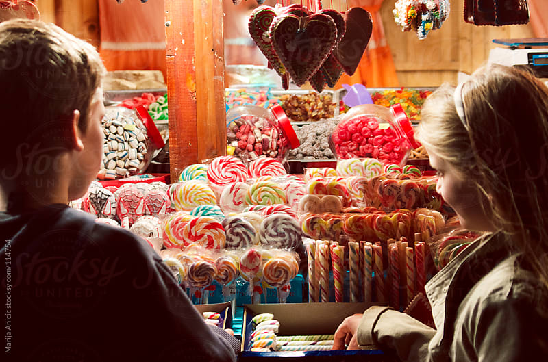 Boy and girl buying lollipops on candy market by Marija Anicic for Stocksy United