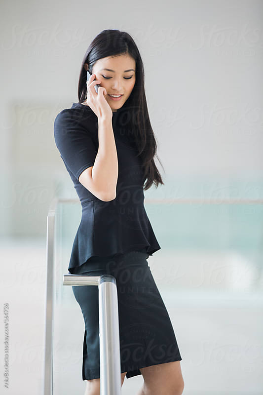 A beautiful asian woman talking on her cell phone by Ania Boniecka for Stocksy United
