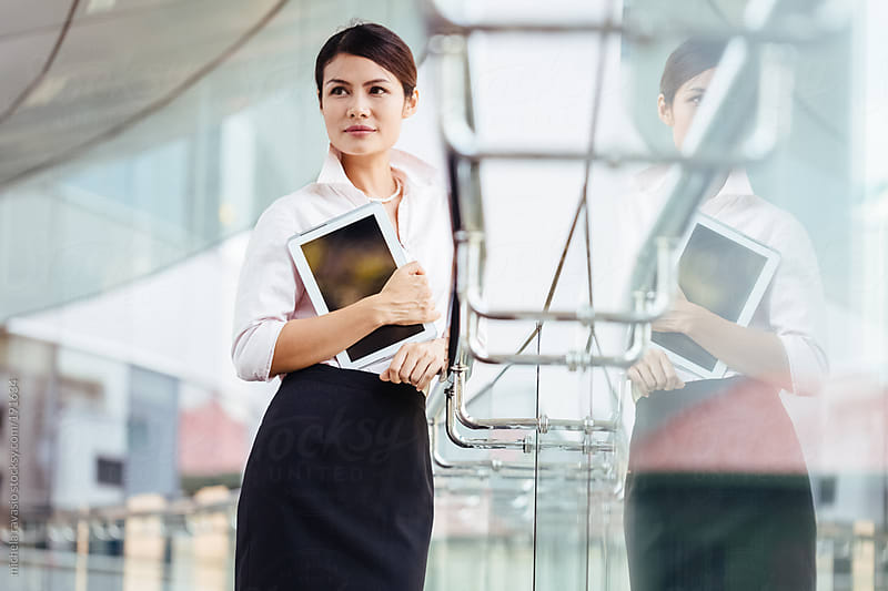 Attractive business woman with her digital tablet by michela ravasio for Stocksy United