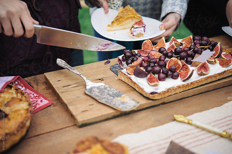 Cutting delicious cake with figs  by Adrian Cotiga for Stocksy United