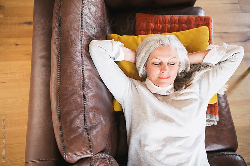 Senior woman lying on the sofa, relaxing. by Lilly Bloom for Stocksy United