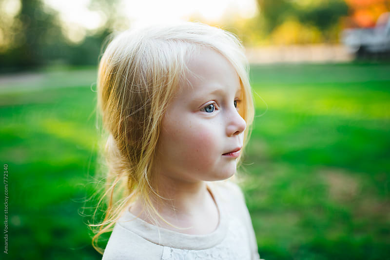 Profile Portrait of Young Girl Against Green Grass by Amanda Voelker for Stocksy United