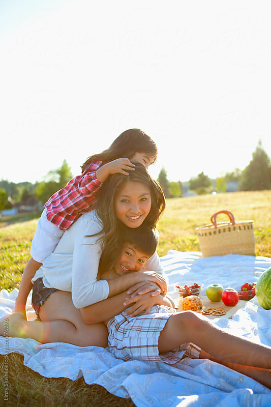 Happy multiracial family hugging at summer picnic by Linzy Slusher for Stocksy United