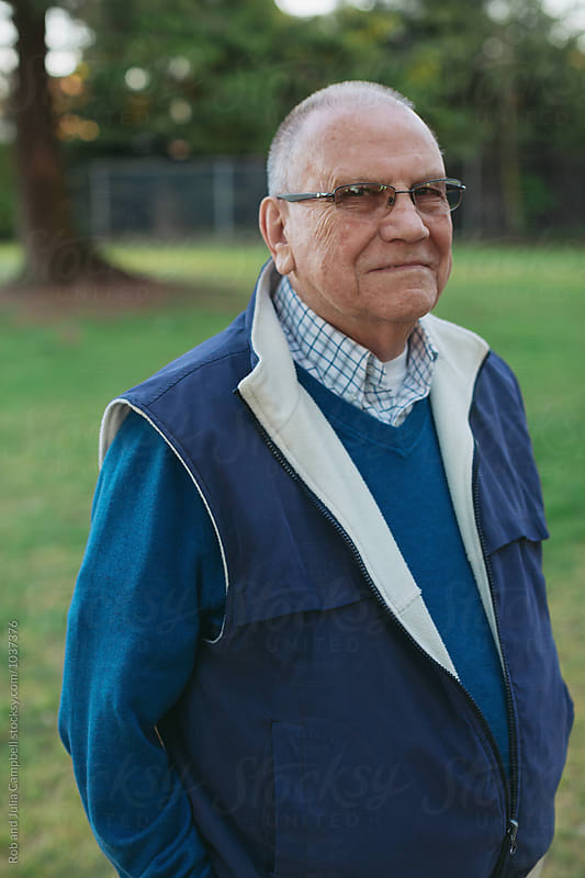 Happy, caucasian senior man looking at camera - outside on spring day by Rob and Julia Campbell for Stocksy United