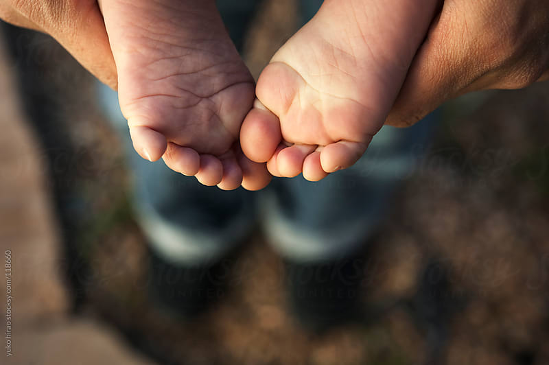 Baby's small feet over parent's legs by yuko hirao for Stocksy United