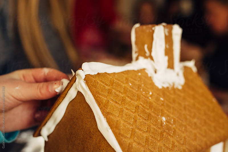 Young girl's hand working on a gingerbread house by Gabriel (Gabi) Bucataru for Stocksy United