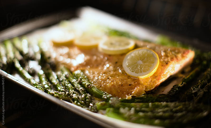 Roasted salmon and asparagus on parchment paper in the oven by Carolyn Lagattuta for Stocksy United