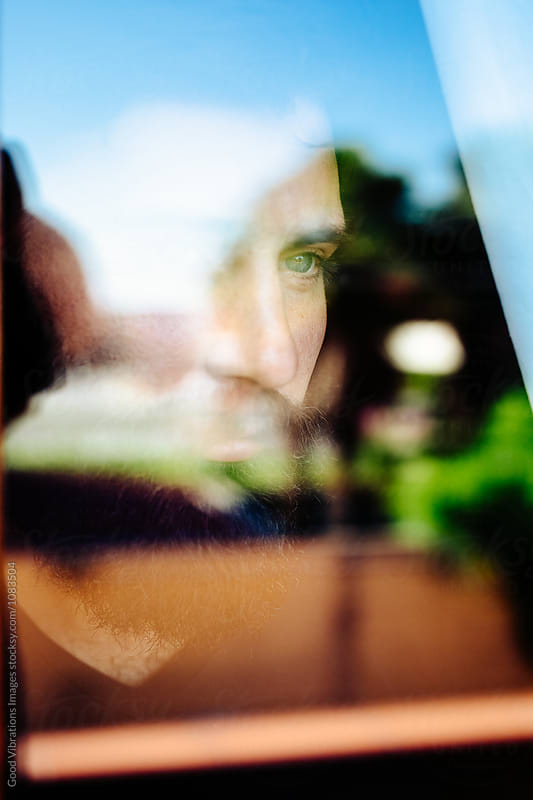 Man looking through a window by Good Vibrations Images for Stocksy United